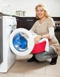 Blonde langhaarige Frau, die zu Hause Waschmaschine verwendet Hausfrau, die zu Hause Waschmaschine verwendet Lizenzfreies Stockbild