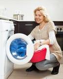 Blonde langhaarige Frau, die zu Hause Waschmaschine verwendet Lächelnde Hausfrau, die Waschmaschine verwendet Stockfoto