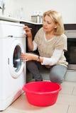 Blonde langhaarige Frau, die zu Hause Waschmaschine verwendet reife Frau, die Waschmaschine verwendet Stockbilder