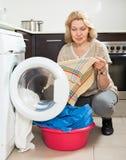 Blonde langhaarige Frau, die zu Hause Waschmaschine verwendet Unglückliche Frau, die Waschmaschine verwendet Lizenzfreies Stockbild