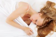 Blonde langhaarige Frau in ihrem Bett Stockfotografie