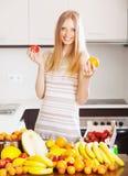 Blonde langhaarige Frau mit Haufen von reifen Früchten Stockfotos