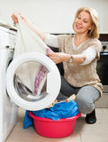 Blonde langharige vrouw die wasmachine thuis met behulp van Stock Fotografie