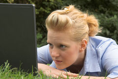 Blonde with laptop. Closeup portrait of a pretty blonde laying on the grass and looking at laptop screen Royalty Free Stock Images