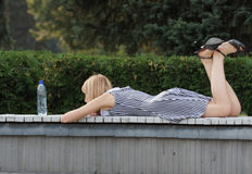 Blonde laying down on bench Stock Images