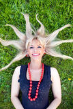 The blonde laying on a grass with scattered hair Royalty Free Stock Image