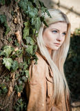 Blonde leaning on Tree. Full with Ivy royalty free stock photography