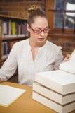 Blonde Lehrerlesebücher in der Bibliothek Lizenzfreie Stockfotografie