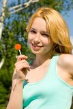 Blonde licking candy in the park Stock Photo