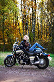 The blonde lies on the big motorcycle Stock Image