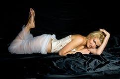 Blonde lies  black satin fabrics Royalty Free Stock Image