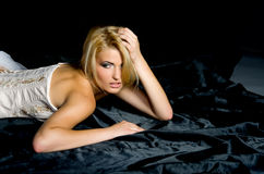 Blonde lies  black satin fabrics Royalty Free Stock Photo