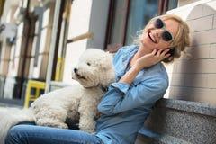 Blonde lindo con el perro del blanco de Bichon Frise Imágenes de archivo libres de regalías
