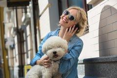 Blonde lindo con el perro del blanco de Bichon Frise Imagenes de archivo