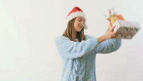 Blonde lindo en el baile del sombrero del ` s de santa con los regalos festivos en un fondo blanco almacen de video