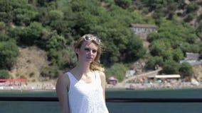Blonde lindo en el vestido que se sienta en un barco en tiempo ventoso almacen de metraje de vídeo