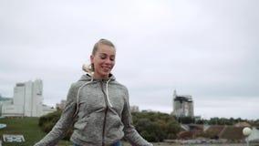 Blonde lindo en la cuerda de salto de la calle Contratan a la muchacha a deportes en el aire fresco almacen de metraje de vídeo