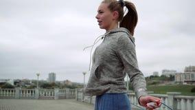 Blonde lindo en la cuerda de salto de la calle Contratan a la muchacha a deportes en el aire fresco metrajes