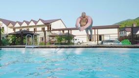 Blonde lindo joven en un salto azul del traje de baño en la piscina Slowmo metrajes
