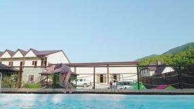 Blonde lindo joven en un salto rojo del traje de baño en la piscina Slowmo almacen de metraje de vídeo