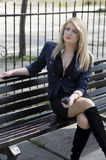 The blonde listens to music, in park on a bench Stock Images