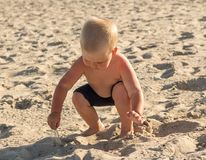 Blonde boy on the beach plays with sand. Blonde little boy on the beach plays with bright beautiful sand Stock Photography