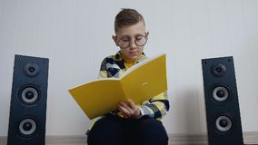 The blonde little boy in glasses with textbook sits on floor at home and records something in there interesting at. Notebook. The pupil does the job that was stock footage