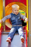 Blonde little boy sits on a childrens slide at the playground Royalty Free Stock Image
