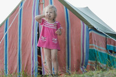Blonde little camper girl relaxing near striped vintage canvas tent Royalty Free Stock Photography