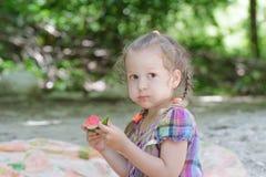 Blonde little girl biting juicy watermelon slice on beach picnic. Blonde little girl biting juicy watermelon slice on summer beach picnic stock photography