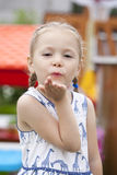Blonde little Girl Blowing a Kiss, on summer park background Royalty Free Stock Images