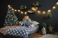 Blonde little girl in blue dress sits on a bed in Christmas dark room Royalty Free Stock Photos
