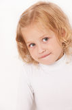 Blonde little girl dressed in white. Biting her lip on  white background Stock Photography