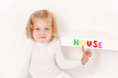 Blonde little girl dressed in white. Stuck word  house of colorful letters  on the shelf Royalty Free Stock Photo