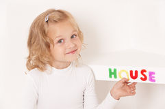 Blonde little girl dressed in white. Stuck word  house of colorful letters  on the shelf Royalty Free Stock Photography