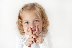Blonde little girl  dressed in white. Standing and puts her fingers to her mouth in the form of letters H Stock Photos