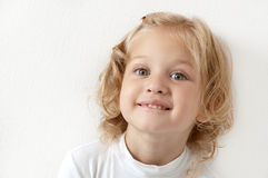 Blonde little girl  dressed in white. Blonde little girl dressed in white biting her lip on  white background Stock Photography