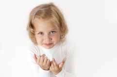 Blonde little girl  dressed in white. Looking directly at the camera on a white background Royalty Free Stock Photo