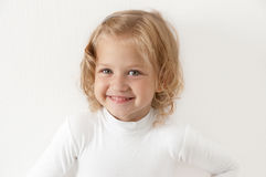 Blonde little girl  dressed in white. Blonde smiling little girl  dressed in white looking directly at the camera on a white background Stock Photography