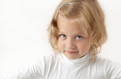 Blonde little girl  dressed in white. Looking directly at the camera on a white background Royalty Free Stock Photography