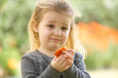 Blonde Little Girl Holding a Flower Stock Photo