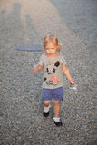 Blonde little girl illuminated by sun rays walking down a gravel path Stock Photos