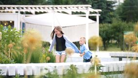 Blonde little girl and more young blond boy walking in the park royalty free stock image