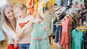 Blonde little girl with mother buying sweatshirt - kids clothes in store Royalty Free Stock Image