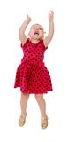 Blonde little girl in a red polka dot dress jumps stock photo
