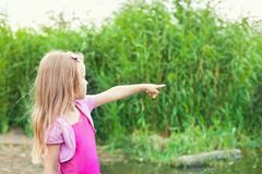 Blonde little girl shows forefingers aside Stock Photo
