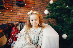 Blonde little girl sitting by the christmas tree stock photo