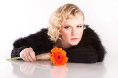 Blonde lockige Frau mit einer Blume Stockfoto