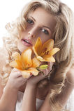 Blonde lockige Frauenholdinglilie Lizenzfreie Stockbilder
