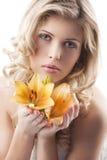 Blonde lockige Frauenholdinglilie Stockbild